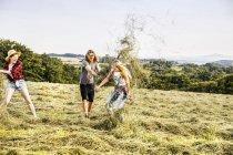 Amici spensierati che giocano con fieno in un campo — Foto stock