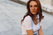 Ritratto di giovane donna rossa seduta nello skatepark e che pensa — Foto stock