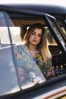 Jeune femme s'asseyant dans un van et jouant la guitare — Photo de stock