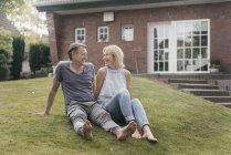 Счастливая зрелая пара сидит в саду дома — стоковое фото