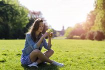 Young woman sitting in park and holding flowers — Stock Photo