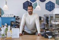 Verticale du propriétaire confiant derrière le compteur d'un café — Photo de stock