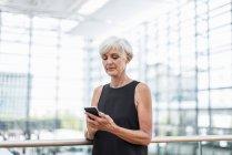 Seniorin steht am Geländer und benutzt Handy — Stockfoto