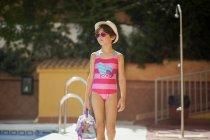 Bambina in costume da bagno che cammina in piscina in estate — Foto stock