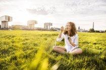 Alemanha, Colônia, retrato de jovem feliz comendo geléia no prado — Fotografia de Stock