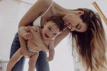 Allegro madre giocare con bambino figlio a casa — Foto stock