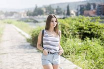 Giovane donna sorridente che cammina su un sentiero rurale in estate — Foto stock