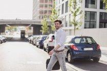 Hombre de negocios sonriente con bolsa para portátil en la calle de cruce de la ciudad - foto de stock