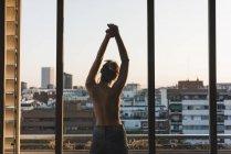 Вид сзади на топлесс молодой женщины, стоящей на балконе — стоковое фото