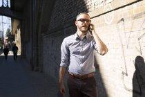 Empresário no celular andando na cidade — Fotografia de Stock