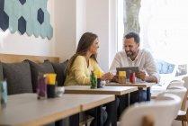 Jeune femme et homme heureux avec tablette dans un café — Photo de stock