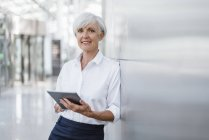 Portrait of smiling senior businesswoman holding tablet while leaning on wall — Stock Photo