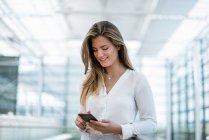 Sorrindo jovem mulher de pé em trilhos usando telefone celular — Fotografia de Stock