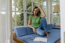 Smiling mature woman sitting on couch at home with book — Stock Photo