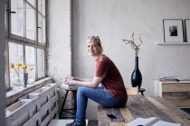Portrait of smiling woman with coffee mug sitting on desk in loft — Stock Photo