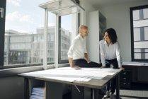 Due architetti che lavorano in ufficio, discutono di progetti sul tavolo — Foto stock