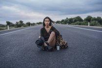 Портрет автостопом молодої жінки з рюкзаком і напоєм сидячи на смузі — стокове фото