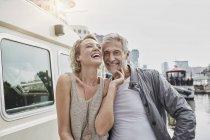 Мужчина и девушка с разницей в возрасте смеются рядом с яхтой — стоковое фото