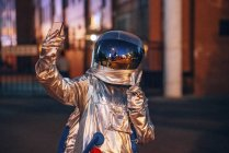 Spaceman in city at night taking a selfie with smartphone — Stock Photo