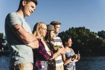 Gruppo di amici in piedi in acqua guardando fuori — Foto stock