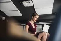 Businesswoman in office wearing burgundy dress and using laptop — Stock Photo