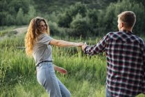 Romantic couple having fun in nature holding hands — Stock Photo