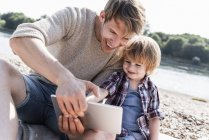 Father and son playing on digital tablet at riverside — Stock Photo