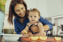 Mother and baby daughter eating apple chunks in kitchen — Stock Photo