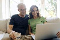 Sorridente coppia matura seduta sul divano a casa condivisione laptop — Foto stock