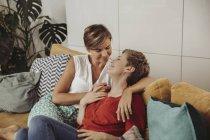 Счастливая лесбийская пара обнимается на диване — стоковое фото