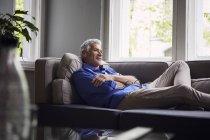 Взрослый мужчина лежит дома на диване — стоковое фото