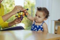 Мать и дочка играют дома за столом — стоковое фото