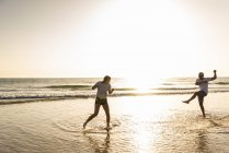 Jovem casal se divertindo na praia, salpicando água no mar — Fotografia de Stock