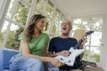Mature couple sitting on couch at home with man playing toy electric guitar — Stock Photo