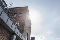 Бизнесмен, стоящая на террасе промышленного здания — стоковое фото