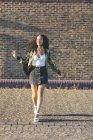 Sorridente giovane donna con i capelli ricci che cammina davanti al muro di mattoni — Foto stock