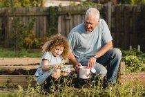 Kleines Mädchen mit ihrem Onkel im Garten — Stockfoto