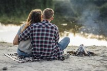 Romantic couple sitting at riverside near campfire in nature — Foto stock