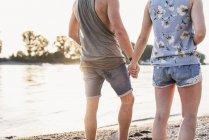 Junges Paar läuft Händchen haltend am Flussufer — Stockfoto