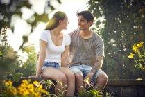 Romantisches junges Paar, das auf einer Mauer in einem Park sitzt, die Arme umschlungen — Stockfoto