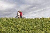 Couples aînés avec le baiser de bicyclette dans le paysage rural sous le ciel nuageux — Photo de stock