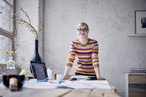 Portrait of smiling woman standing at desk in design loft — Stock Photo