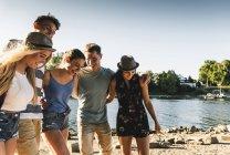 Gruppo di amici felici a braccetto sul lungofiume — Foto stock