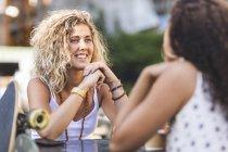 Felizes amigas conversando juntas à mesa ao ar livre — Fotografia de Stock