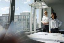 Due architetti in piedi in ufficio, guardando fuori dalla finestra, telefono cellulare sul tavolo — Foto stock