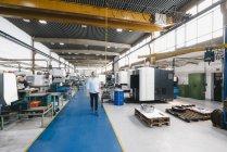 Businessman walking through factory workshop — Stock Photo