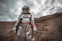 Homem do espaço explorando planeta sem nome sob céu nublado — Fotografia de Stock