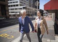 Allegro coppia matura a piedi in città tenendosi per mano — Foto stock