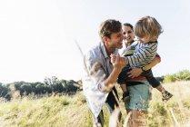 Счастливая семейная прогулка по берегу реки в солнечный летний день — стоковое фото