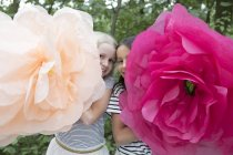 Two smiling girls with two oversized artificial flowers — Stock Photo